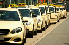 Taxi. Row of empty, yellow taxi cabs waiting for passengers in a city