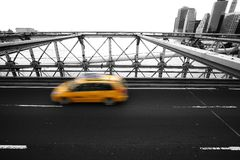 Taxi  rushing on new york brooklyn bridge. Yellow taxi rushing on brooklyn bridge in new york against city buildings Royalty Free Stock Images