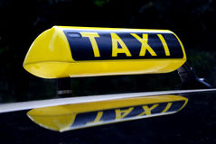 Taxi sign. Yellow neon taxi sign mirroring in the car roof Stock Photo