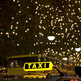 Taxi sign. Yellow taxi sign in front of many lights at night Royalty Free Stock Photos