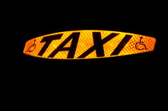 Taxi Sign. Lit up showing the word Taxi and the disabled symbol Royalty Free Stock Images