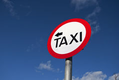 Taxi sign. With arrow against blue sky Stock Photography