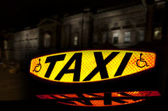 Taxi Sign 4. Taxi sign lit up showing the word Taxi and the disabled symbol with a reflection Royalty Free Stock Photos