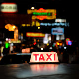 Taxi sign. At night in Hong Kong, with the city in background Royalty Free Stock Photos