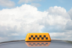 Taxi sign. Taxi a sign on a roof of the car against clouds Royalty Free Stock Image