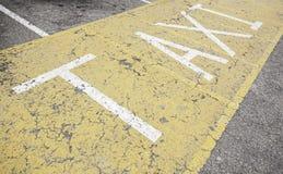 Taxi sign on asphalt Royalty Free Stock Photo