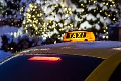 Taxi sign on the background of night winter city. The taxi sign on the background of night winter city royalty free stock photo