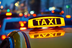 Taxi sign on car at evening in the city street. Yellow taxi sign on cab car at evening or night in the city street royalty free stock photos