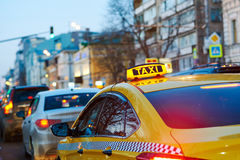 Taxi sign on car at evening in the city street Stock Photo