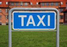 Taxi Sign Closeup with Building and Grass Background Stock Image