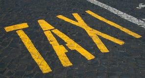 Taxi sign on cobblestones Stock Photos