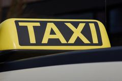 Taxi sign on a German taxi car. Yellow taxi sign on a German cab, photographed close up with a dark background Stock Photos