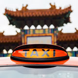 Taxi sign of a London taxi in front of the Chinatown gate in London Stock Photos