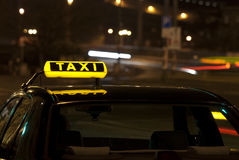 Taxi sign at night. A photo of a taxi sign on a top of a taxi car at night Stock Image