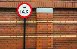 Taxi sign red brick wall Royalty Free Stock Photo