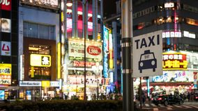 Taxi sign under bright neon and advertisement lights at Kabukicho in the Shinjuku, Tokyo, Japan. Tokyo, Japan - August 2018: Taxi sign under bright neon and stock images