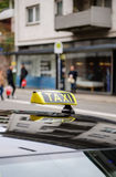Taxi sign waiting for customers in city with defocused pedestria. Ns and buildings Royalty Free Stock Images