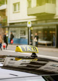 Taxi sign waiting for customers in city with defocused pedestria. Ns and buildings Stock Image