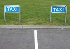 Taxi Signs at Empty Parking Place with Green Background Royalty Free Stock Image