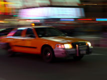 Taxi speeds down the street. A New York City taxi speeds down the street royalty free stock photography