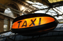 Taxi at the Station. Taxi light on a traditional black cab.  Taken inside a beautiful Victorian station building in the UK Stock Photography