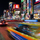 A taxi streaks by at night in Tokyo, Japan. Shinjuku Tokyo is one of the busiest areas in the world Stock Image