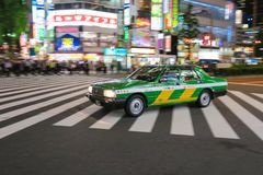 A taxi streaks through Shinjuku Crossing in Tokyo, Japan. Shinjuku Tokyo is one of the busiest areas in the world Royalty Free Stock Image