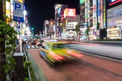 A taxi streaks by in Tokyo, Japan. Shinjuku Tokyo is one of the busiest areas in the world Royalty Free Stock Photo