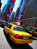 Taxi in Times Square. Yellow taxi in front of the neon signs of Times Square during daylight in New York Royalty Free Stock Image