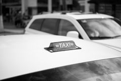 Taxi top sign on white cab roof Stock Photos