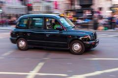 Taxi tradicional de Londres en la falta de definición de movimiento Imagen de archivo libre de regalías