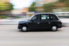 Taxi tradicional de Londres en la falta de definición de movimiento Imagenes de archivo