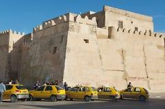 Taxi väntar på passagerare in från av den medina väggen i Sfax, Tunisien royaltyfri foto