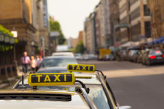 Taxi waiting in front of another one. Two taxis waiting for a businessman at the street in city. Nice depth of field. With copy space Stock Photography