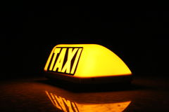 Taxi yellow sign. Close up on a yellow taxi cab sign turned on Stock Photography