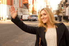 Taxi. Young woman hailing a taxi stock photos
