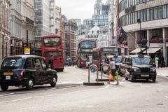 Taxiar och röda bussar London Royaltyfri Bild