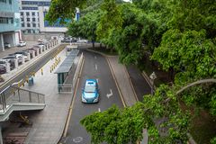 Taxiauto bij taxieinde wordt die op passagier onder groene die bomen wachten van het viaduct worden bekeken geparkeerd dat royalty-vrije stock afbeelding