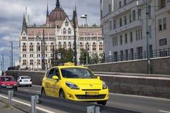 Taxiauto in de straat van Boedapest tegen de achtergrond van het Hongaarse Parlement Royalty-vrije Stock Afbeeldingen