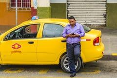 Taxibestuurder Chatting met zijn Cellphone stock foto