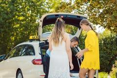 Taxibestuurder die bagage van vrouwen in boomstam van auto zetten stock foto's