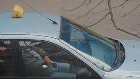 Taxibestuurder die in zijn geparkeerde auto rusten terwijl ter beschikking het controleren van zijn mobiele telefoon De meeste or stock footage