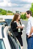Taxichaufför och passagerare framme av bilen Arkivbilder