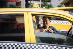 Taxichaufför som kör den lyckliga klienten för bil som betalar pengar Arkivfoton