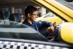 Taxichaufför som kör lyckliga räknande pengar för bil Arkivbilder