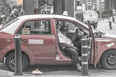Taxifahrer, der in seinem Taxi in Kuala Lumpur, Malaysia ein Schläfchen hält lizenzfreie stockbilder