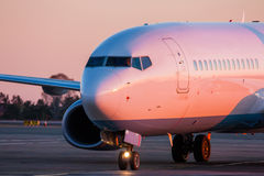 Taxiing aircraft on the main taxiway. Taxiing aircraft in the morning crimson Royalty Free Stock Image