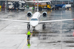 Taxiing aircraft parking at the airport after landing. Man indicates the distance to the stop Royalty Free Stock Photos