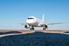 Taxiing a white passenger airplane on the airport apron. Taxiing a white passenger aircraft on the airport apron stock photos