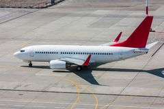 Taxiing white and red aircraft on the airport apron Stock Images